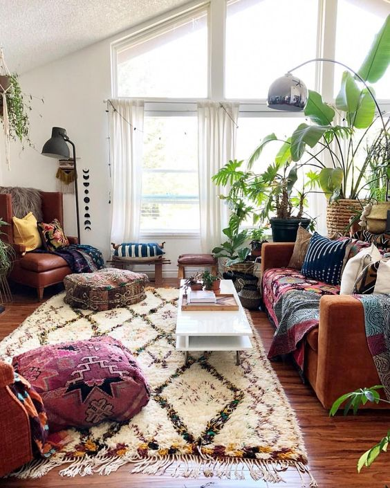a bright boho space with printed rugs and throws, potted greenery and cool floor lamps and cushions