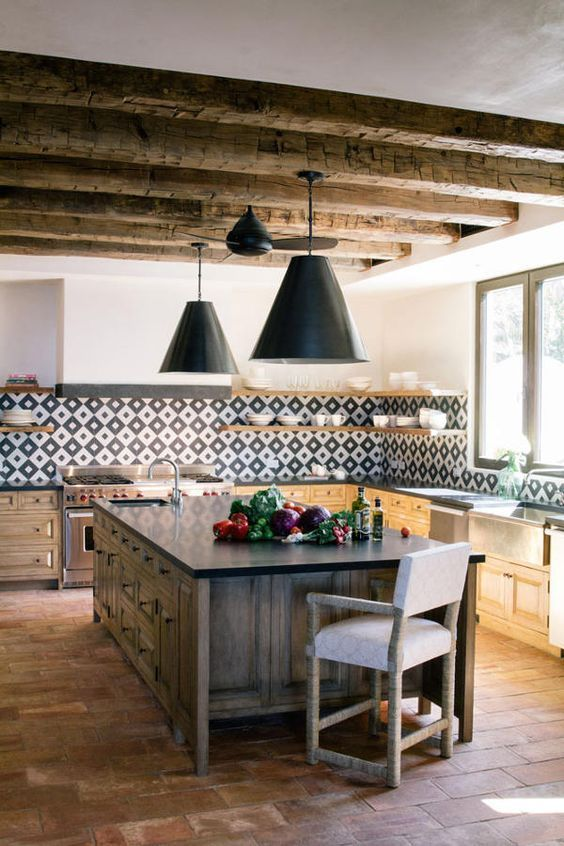 a bright modern Spanish kitchen with wooden beams, a printed tile backsplash, pendant lamps and a heavy wooden kitchen island