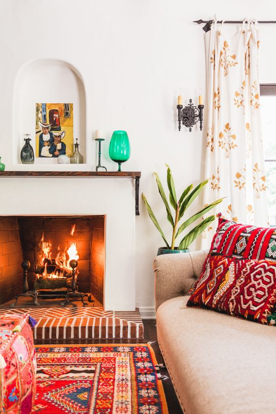 a bright modern Spanish space with colorful printed textiles, bright touches, white walls and a fireplace, potted plants