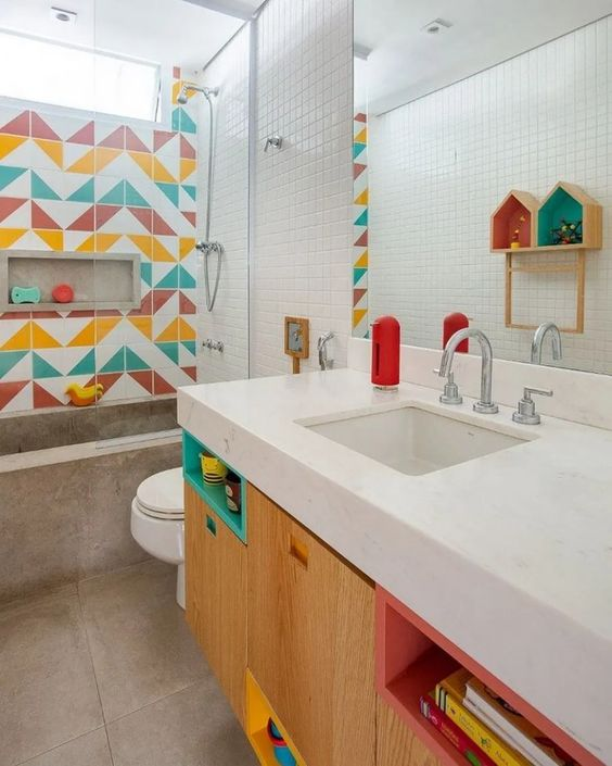 a bright modern kids' bathroom with a colorful tile wall, bright niches and a concrete bathroom is a fresh idea