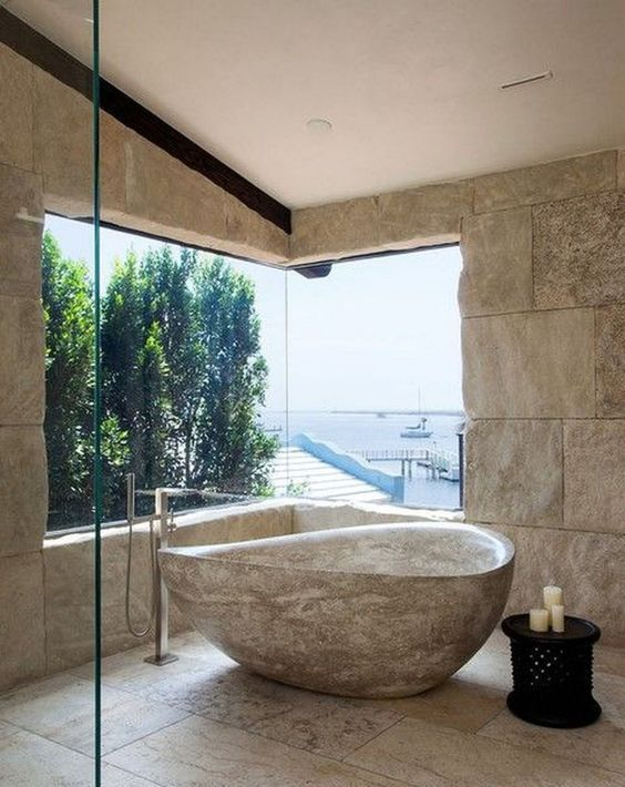 a catchy bathroom with a sea view, stone walls, stone tiles on the floor and a catchy stone bathtub
