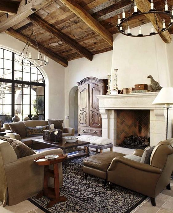 a chic Spanish living room with white plaster walls, reclaimed wood ceiling with beams, neutral furniture and vintage chandeliers