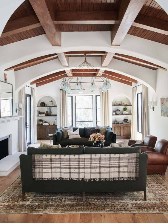a chic Spanish living room with white walls and ceilings, wooden beams, dark furniture and a catchy chandelier