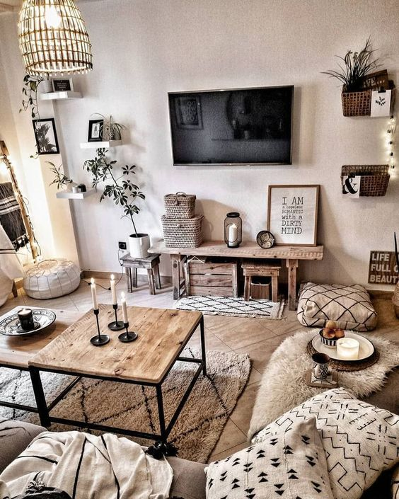 a chic neutral boho room with wooden furniture, lots of potte greenery, various prints and touches of black