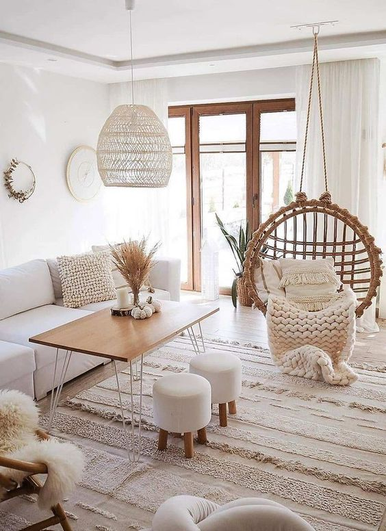 a clear white boho room with a round rattan chair, a wicker lampshade, boho rugs and faux fur plus natural wood