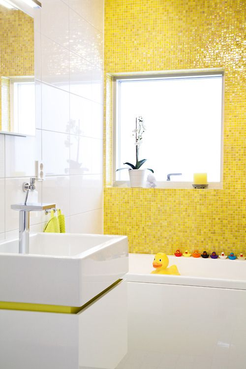 a colorful and fun kids' bathroom in bright yellow and white, some bright accessories and colorful ducks