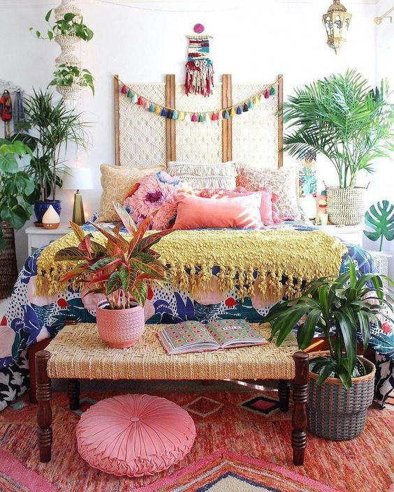 a colorful boho bedroom with all bright textiles and linens, lots of potted plants, a colorful tassel garland and Moroccan lamps
