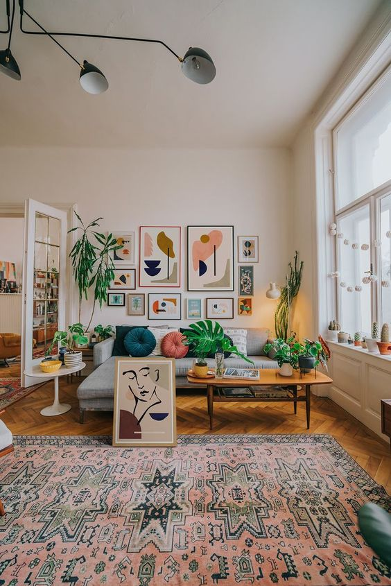 a colorful boho meets mid-century living room with a bright gallery wall, a printed rug and colorful pillows plus greenery