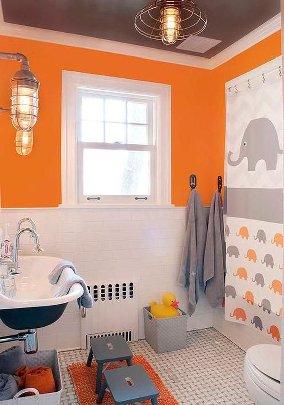 a colorful kids' bathroom in grey, orange and white, with an oversized elephant artwork, grey stools, vintage lamps