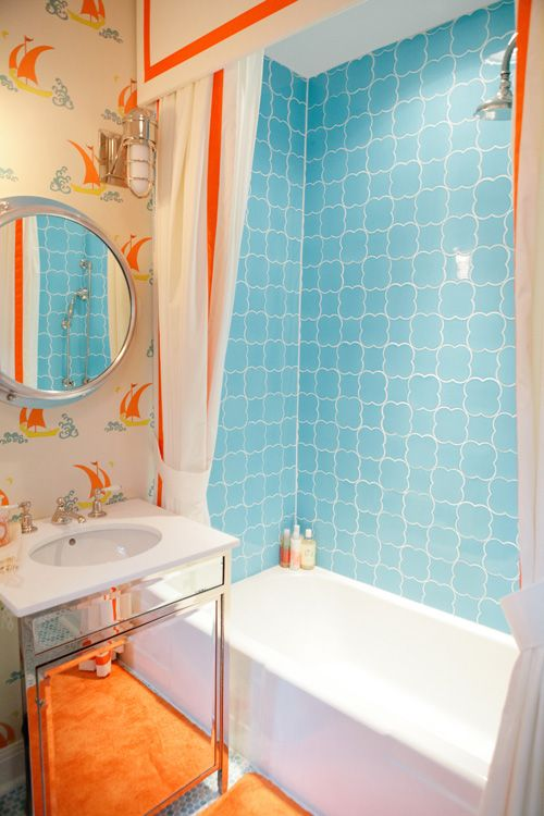 a colorful kids' bathroom in light blue and orange, with a seascape theme, bright tiles and vintage-inspired wallpaper