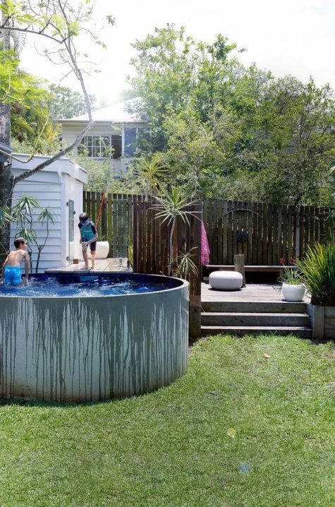 a contemporary deck with some wooden furniture and a raised round tank pool next to it are perfect for kids