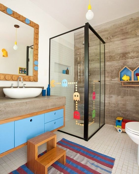 a contemporary kids' bathroom with a colorful vanity, bright shelves, a colorful rug, colorful decals on the shower