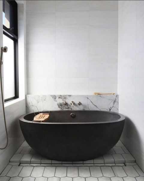 a contemporary monochromatic bathroom with a blakc stone wall, marble and geometric tiles and dark fixtures for a bold look