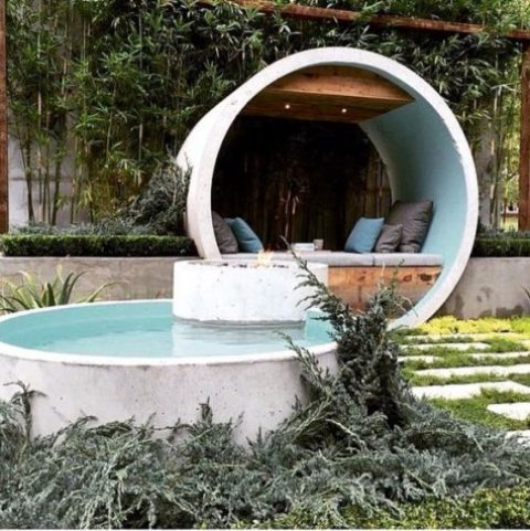a contemporary outdoor space with a terrace placed inside a white concrete circle and a matching pool