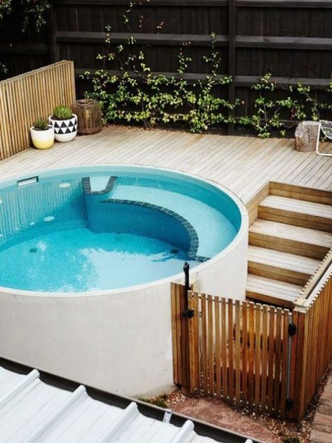 a contemporary round pool with a light-colroed wooden deck and some potted plants to make the space fresh