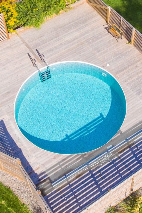 a contemporary wooden deck with a bench and a large round pool that invites you in looks amazing