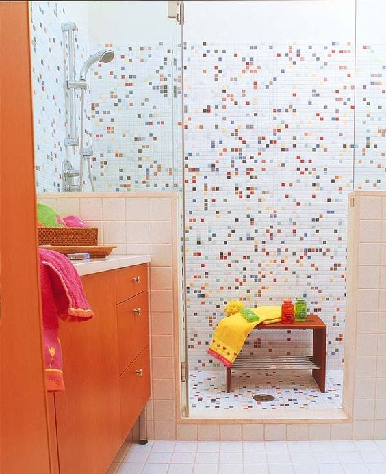 a cool colorful kids' bathroom with mosaic tiles in the shower space and an orange vanity is all the fun and cheerfulness