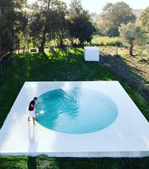 a cool minimalist round pool with a white frame around looks very eye-catching and allows relaxing on this watery deck, too