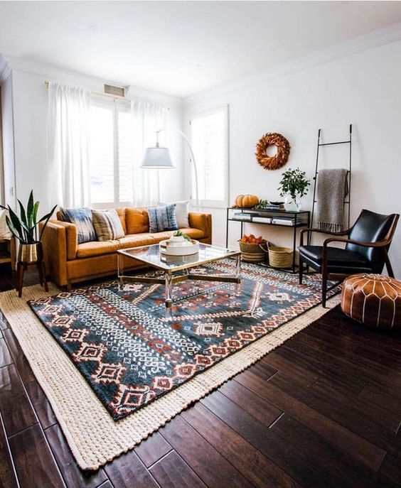 a cozy boho living room with layered rugs, leather and velvet furniture, colorful touches and some dramatic black elements