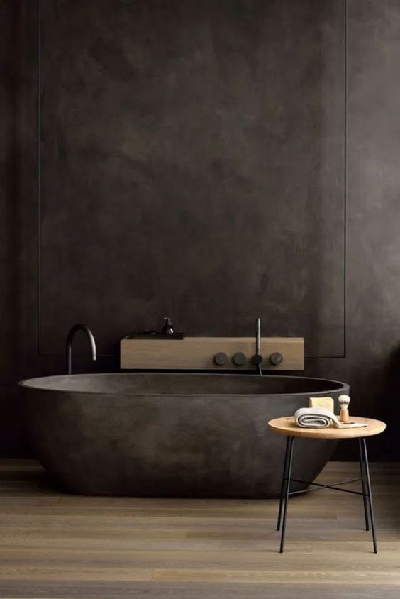 a dark and moody bathroom with a black stone bathtub, a mini side table and a wooden shelf on the wall
