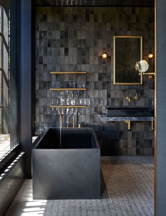 a dark bathroom with bathroom tiles, a black stone square bathtub, a dark vanity, a black sink and gold touches here and there