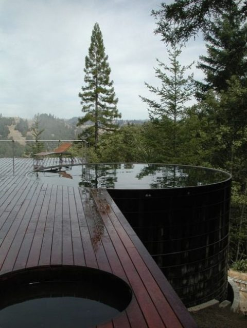 a dark stained wooden deck with a large and deep round pool that features amazing views of the nature around