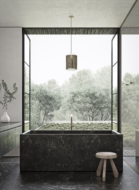 a gorgeous moody bathroom with a black square stone bathtub and matchign floors and a vanity plus a garden view