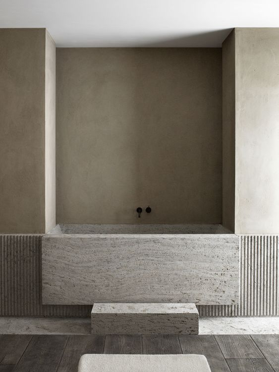 a minimalist bathroom done in neutrals, with a built in stone bathtub and dark wooden floor