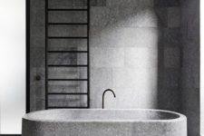 a minimalist granite bathroom with a granite bathtub plus a black ladder is a cool idea for an edgy feel