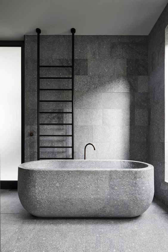 a minimalist granite bathroom with a granite bathtub plus a black ladder is a cool idea for an edgy feel
