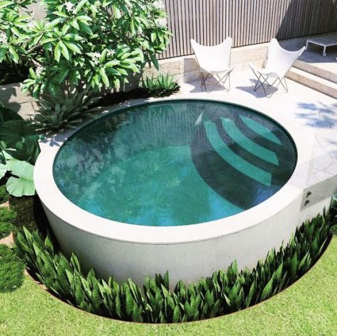 a minimalist round pool with steps surroundded with succulents and with a stone terrace and butterfly chairs
