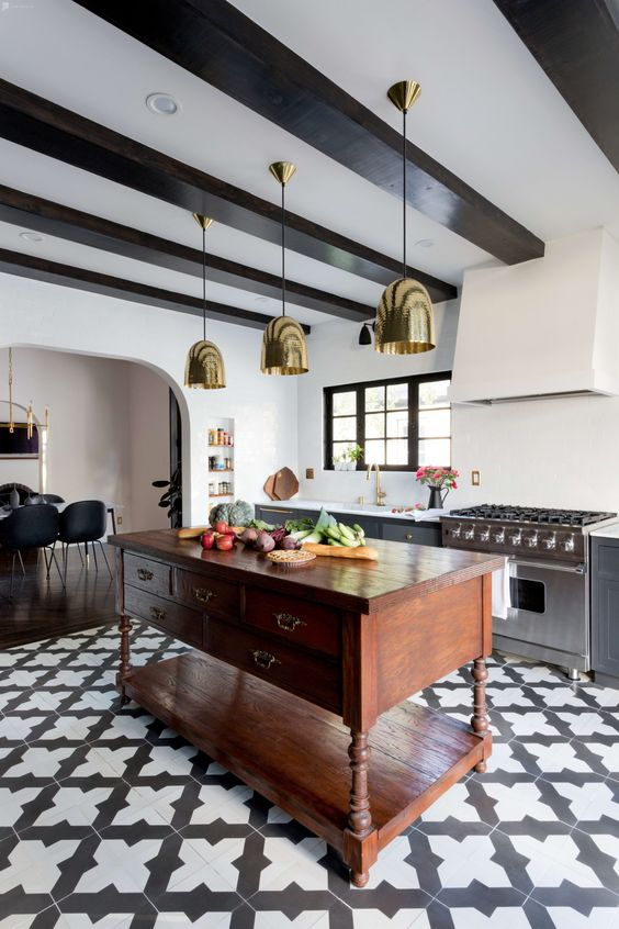 a modern Spanish kitchen with printed tiles, gold pendant lamps, heavy wooden furniture and dark wooden beams