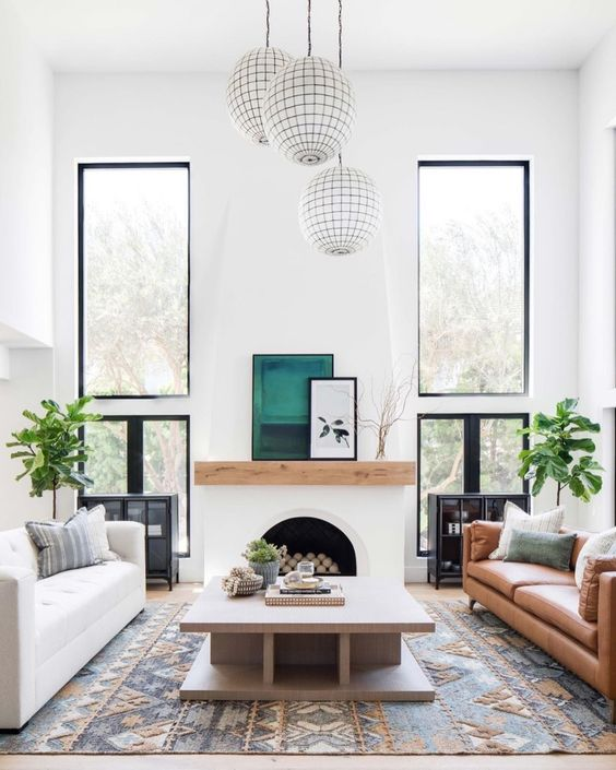 a modern Spanish space with white walls, a faux fireplace, warm-colored furniture and bright touches and prints