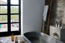 a moody bathroom with a white pebble tile, dark stone on the wall and a dark stone bathtub plus a wooden side table