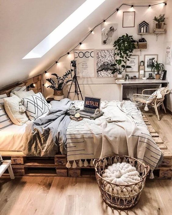 a neutral attic boho space with string lights, greenery in pots, a pallet bed, wicker and rattan furniture