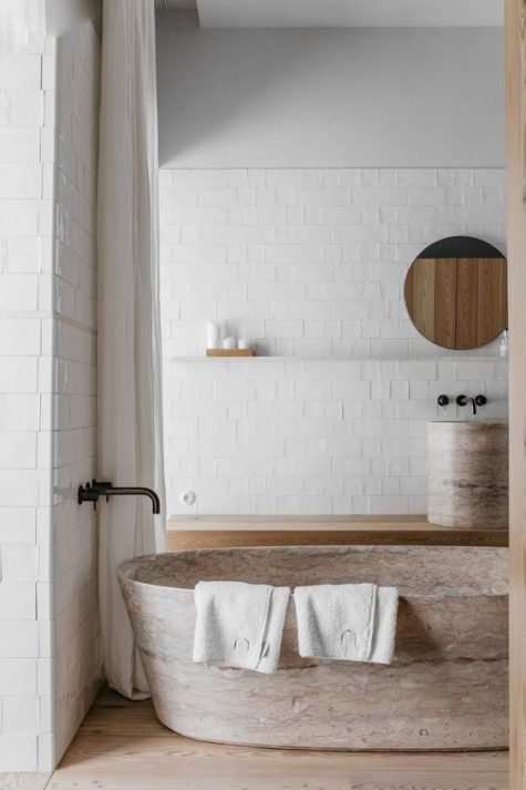 a neutral bathroom with a gorgeous stone bathtub and a matching sink looks refined and very natural