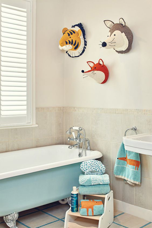 a neutral bathroom with a light blue tub, colorful and fun towels and toy animal heads on the wall