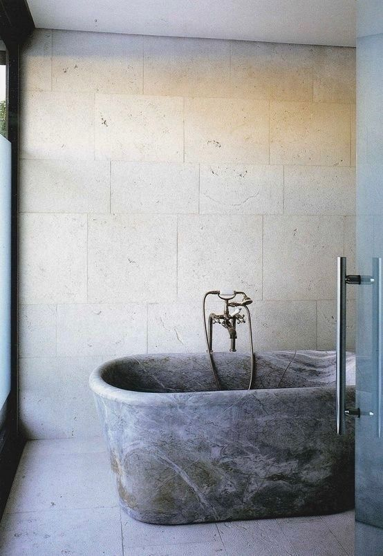 a neutral bathroom with textural tiles on the walls and floor, a grey stone bathtub and dark metal fixtures