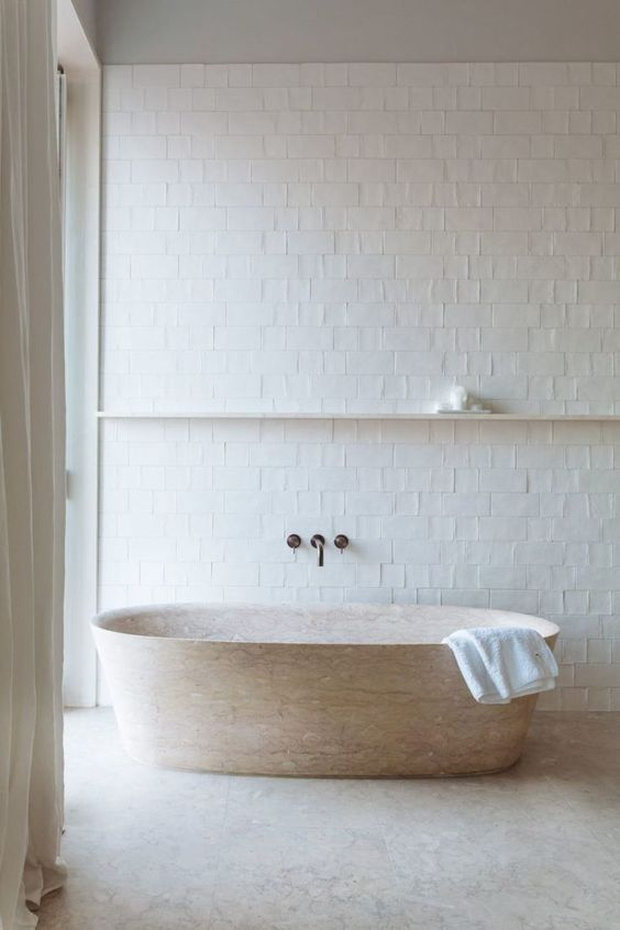 a neutral bathroom with white tiles, a stone bathtub and a floating shelf for an airy and serene feeling in the space