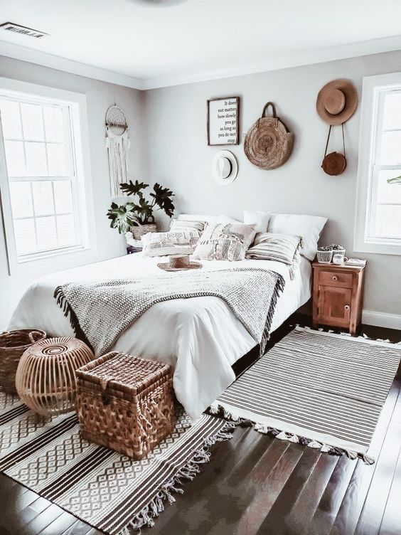 a neutral boho bedroom with layered crochet textiles, woven and wicker details, a dream catcher on the wall