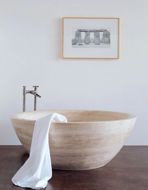 a neutral contemporary bathroom with a bowl-like stone bathtub and a catchy artwork for a modern feel