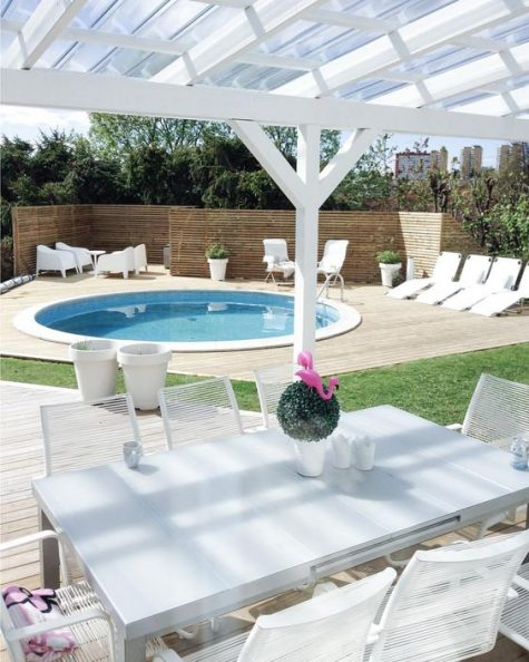 a neutral contemporary space with loungers and white garden furniture and a round pool clad in white, too