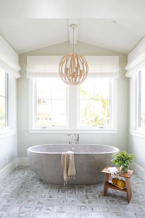 a neutral farmhouse bathroom with printed tiles, a neutral stone bathtub and a round chandelier looks serene