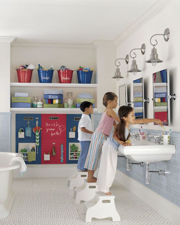 a neutral kids' bathroom with blue and red touches, accessories and a storage board for everyone