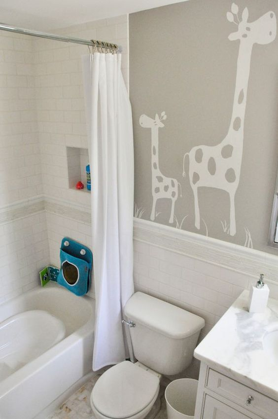 a neutral kids' bathroom with giraffes on the wall, some colorful touches and all neutral everything