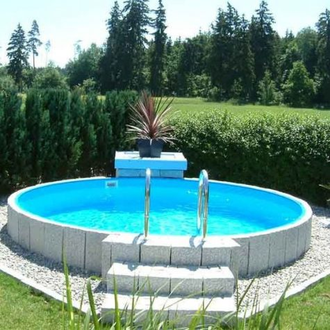 a raised round pool clad with stone and accented with a single statement plant opposite the stairscase