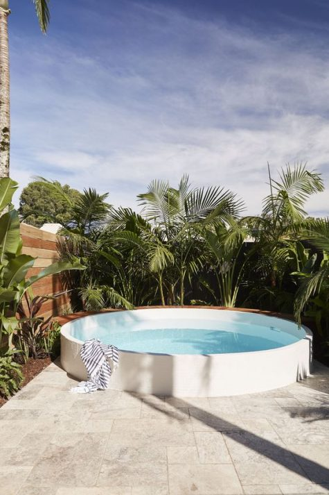 a raised round pool surrounded with tropical plants is a stylish and minimal option to go for