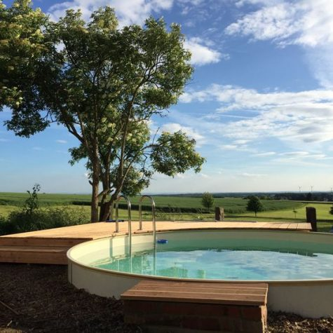 a raised round pool with a minimal wooden deck and a metal staircase to enjoy the views