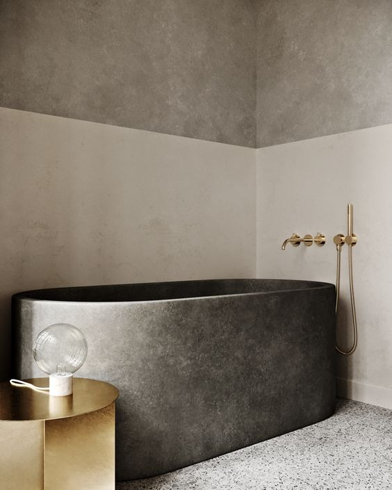 a refined and minimalist bathroom with color block walls, a stone bathtub and a polished gold side table and fixtures