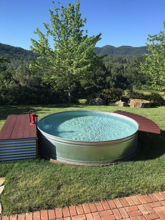 a round tank pool with a small deck with stroage and another curved piece to relax on can be DIYed